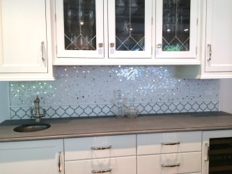 These small metallic tiles add just enough sparkle to a plain white kitchen. Courtesy of Wayne Tile.