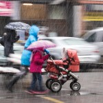 Mother walking in rain stroller